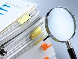 זכוכית מגדלת ליד ערמת מסמכים
